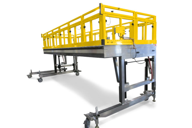 OSHA compliant mobile aluminum work stand with cantilever overreach featuring vertical telescopic guardrails that lower to accommodate obstacles for failsafe fall protection.